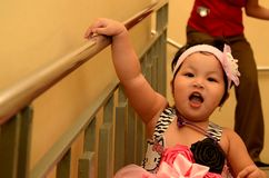 Baby girl having fun at stairs chased by waiter in a birthday party celebration. San Pablo City, Laguna, Philippines - December 22, 2016: Baby girl having fun at royalty free stock images