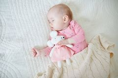 Baby girl having a nap with mouse toy royalty free stock photography