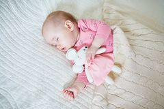 Baby girl having a nap with mouse toy royalty free stock photo