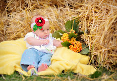 Baby girl on hay in the Ukrainian style Royalty Free Stock Image