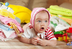 Baby girl with heap of baby's wear Stock Image