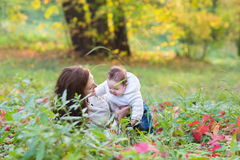 Baby girl held by her mother playing with red autumn leaves Stock Photos