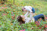 Baby girl held by her mother playing with red autumn leaves Royalty Free Stock Photography