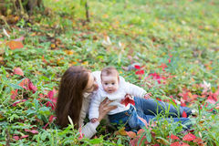 Baby girl held by her mother playing with red autumn leaves Royalty Free Stock Images