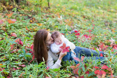 Baby girl held by her mother playing with red autumn leaves Stock Image