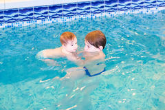 Baby girl and her brother in the swimming pool. Baby girl and her brother playing in the swimming pool stock photography