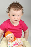 Baby girl with her doll on grey background Royalty Free Stock Photo