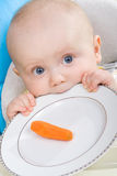 Baby girl and her first carrot. Six months old baby girl before eating her first ever... well... carrot Royalty Free Stock Photo