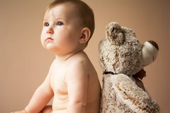 Baby girl and her friend teddy bear Stock Images