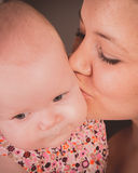 A baby girl and her mother. A baby girl being kissed by her mother stock images