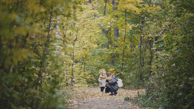 Baby girl with her mother and Teddy Bear walking in autumn park Stock Photo