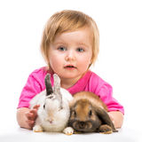 Baby girl  with her rabbits Stock Photo