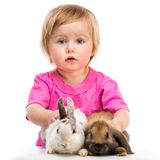 Baby girl  with her small rabbits Stock Image