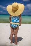 Baby girl in her sun hat on the beach royalty free stock photos