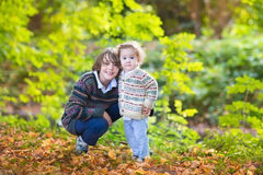 Baby girl and her teen age brother in autumn park. Adorable baby girl and her teen age brother playing together in a beautiful sunny autumn park Stock Photo