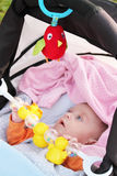 Baby girl and her toys in a baby carriage Royalty Free Stock Photos