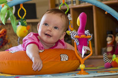 Happy Baby girl toy lying tummy. A happy baby girl lying on her tummy on a play mat with toys Royalty Free Stock Photo