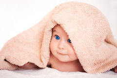 Baby girl is hiding under the beige terry towel Royalty Free Stock Photography