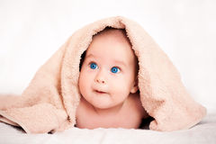 Baby girl is hiding under the beige terry towel Stock Photography