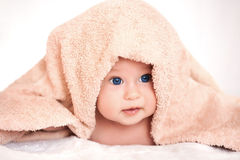 Baby girl is hiding under the beige terry towel Royalty Free Stock Images