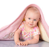 Baby girl is hiding under blanket over white backgroun Stock Photos