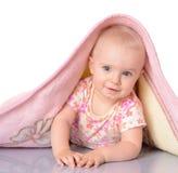 Baby girl is hiding under blanket over white backgroun Stock Photos