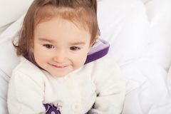 Baby girl is hiding under the white blanket Royalty Free Stock Image