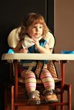 Baby girl in high chair having her food royalty free stock photos
