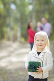 Baby Girl Holding Christmas Gift Outdoors Parents Looking On Royalty Free Stock Photography