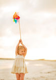 Baby girl holding colorful windmill toy Stock Photos
