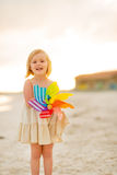 Baby girl holding colorful windmill toy on beach Stock Photo