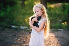 Baby girl holding hands a kitten in the light of sunset Stock Image