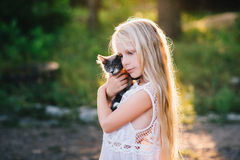 Baby girl holding hands a kitten in the light of sunset Royalty Free Stock Photo