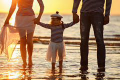 Baby girl holding hands mom and dad and looks in the picture, st Royalty Free Stock Image