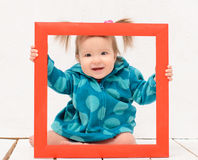 Baby girl holding hands red frame Royalty Free Stock Photography