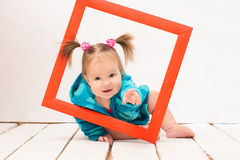Baby girl holding hands red frame Stock Photography