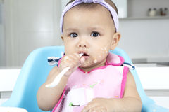 Baby girl holding her spoon in kitchen Royalty Free Stock Photography