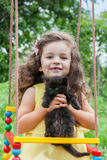Baby girl holding kitten outdoors Royalty Free Stock Photography