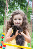 Baby girl holding kitten outdoors Royalty Free Stock Photos