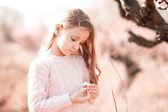Baby girl holding peach flower outdoors Stock Image