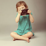 baby girl holding photo camera Stock Photos