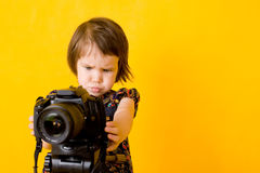 Baby girl holding photo camera. Portrait of baby girl holding photo camera isolated on yellow background Royalty Free Stock Photo