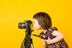 Baby girl holding photo camera. Portrait of baby girl holding photo camera isolated on yellow background Royalty Free Stock Photography