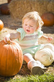 Baby Girl Holding a Pumpkin at the Pumpkin Patch Royalty Free Stock Image