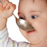 Baby girl holding spoon in mouth Royalty Free Stock Image