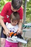 Baby girl holding and working with an electric saw, a chainsaw. Royalty Free Stock Photo