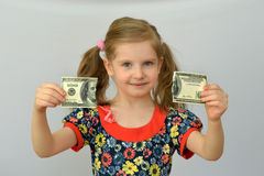 Baby girl holds in hands a torn banknote ,dollar ,banking crisis. Royalty Free Stock Images
