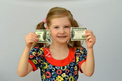 Baby girl holds in hands a torn banknote ,dollar ,banking crisis. Royalty Free Stock Photos