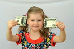Baby girl holds in hands a torn banknote ,dollar ,banking crisis. Stock Image