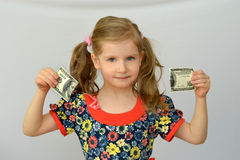 Baby girl holds in hands a torn banknote ,dollar ,banking crisis. Stock Photos
